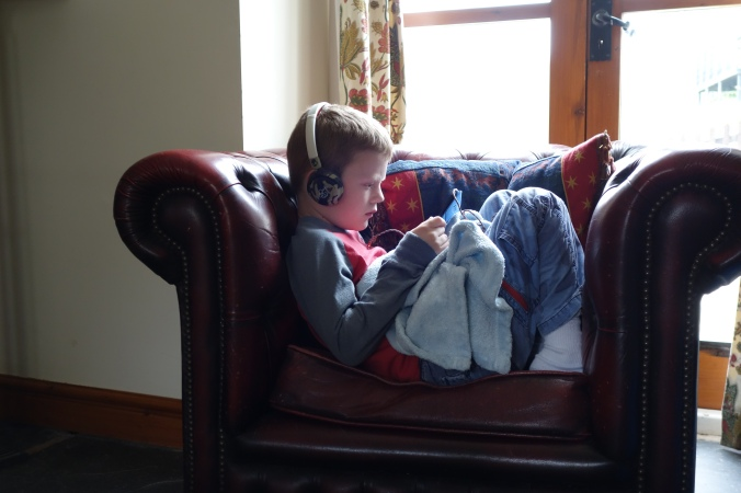 Liam cozy with his ipad and blankie