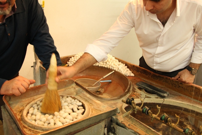 Silk worms are first soaked in water and then he takes this brush to swirl them around
